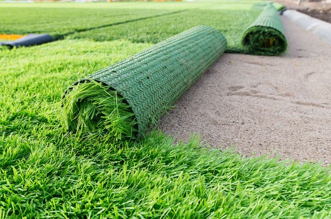 Artificial grass being laid in a customers garden